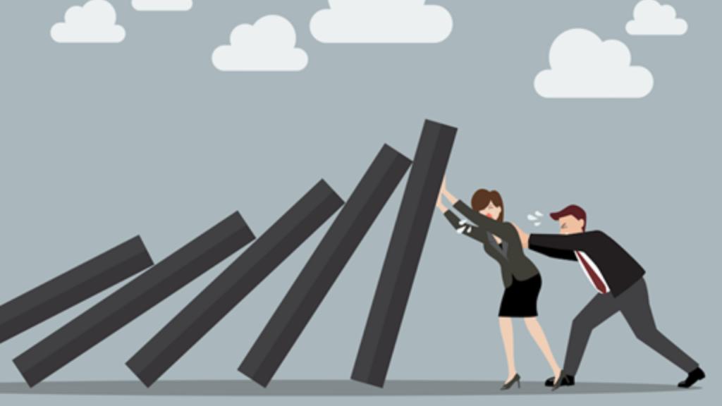 Um homem e uma mulher segurando um efeito dominó de placas maiores que os próprios seres humanos nessa imagem. Ambos estão de cinza e o fundo e os dominós também são cinza.