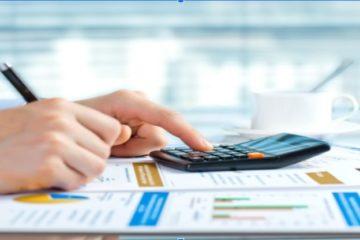 Uma pessoa mexendo em uma calculadora enquanto escreve em um papel