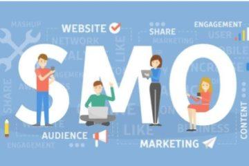 SMO escrito em tamanho grande, enquanto quatro pessoas estão encostadas nas letras, mexendo em celulares, tablets e computadores