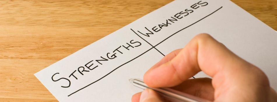 Uma mão escrevendo dentro de um papel as forças e fraquezas