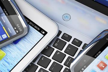 A imagem mostra um notebook e três aparelhos celulares ligados em suas telas de início.