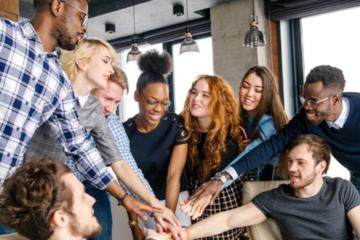 Nove pessoas juntando as mãos. Três delas são negras e o restante é branco. Estão em um escritório.