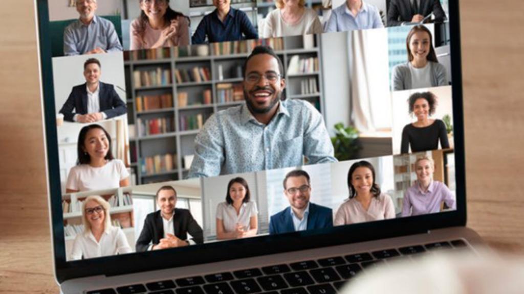 Um laptop com a imagem de várias pessoas. O fundo é marrom.