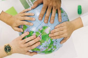 Quatro pessoas colocando a mão no globo terrestre