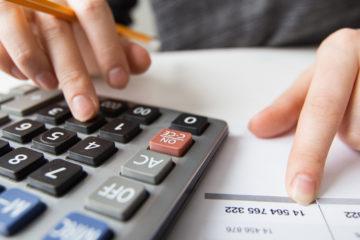 A imagem mostra uma mão mexendo em uma calculadora, que está ao lado de uma folha impressa com números.