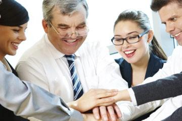 A imagem mostra seis pessoas, vestidas com roupas sociais, em um ambiente de trabalho. Elas estão unidas e sorrindo.
