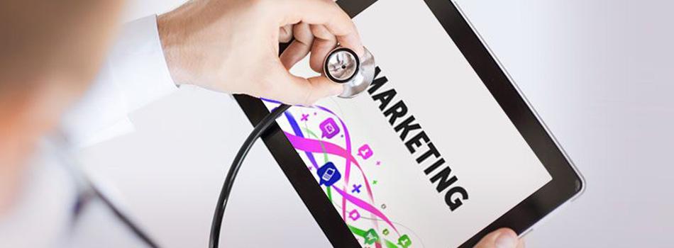 Pessoa utilizando um estetoscópio em uma tela de tablet, com a palavra marketing na tela