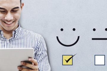 A imagem mostra uma pessoa sorrindo e segurando um tablet. Ao lado estão três ícones que representam índice de satisfação: um rosto feliz, um sério e outro triste.