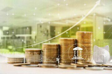 A imagem apresenta cinco pilhas de moedas, formando uma escadinha, ao lado de um cofre de porquinho. Acima das pilhas de moedas, há uma seta, representando um gráfico de crescimento.