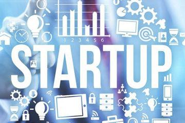 A imagem é azulada e mostra uma mão apontando para a palavra startup. Em volta da palavras tem diversos ícones, como: lâmpada, quebra-cabeça, pessoas, relógio e lupa.