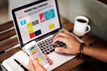 A imagem mostra um notebook com informações sobre marketing estratégico. Também tem uma mão segurando um celular com imagens de gráficos, um caderno com anotações e uma xícara de café.