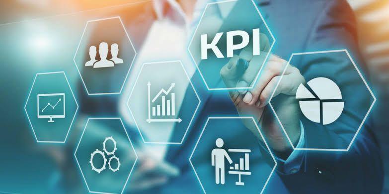 A imagem apresenta uma tela transparente azulada com símbolos de gráficos, engrenagens e a sigla KPI.